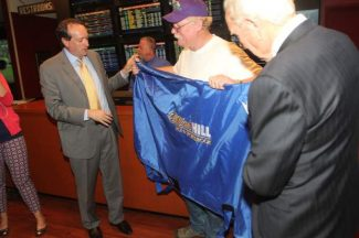 Steve Coburn is presented with a blanket for California Chrome from  William Hill Sportsbook CEO Joe Asher, left, and Sharkey's Casino owner Hal Holder on May 28 at Sharkey's Casino in Gardnerville.