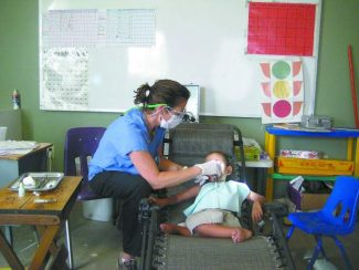 South Lake Tahoe dentist April Westfall works on the mouth of a young boy during one of her many trips abroad. Westfall has visited more than a half dozen countries to practice dentistry in remote places. She will travel to Sudan at the end of August.
