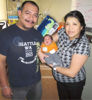 Abraham and Adriana Tapiz show their son, Joshua, who was the first baby born at the South Shore in 2014.
