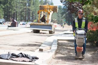 A worker with Sierra Nevada Construction tamps down the ground to prepare for paving on Harrison Avenue that will be done today and tomorrow. The road should be reopened soon, as construction activities shift to Riverside Avenue.