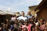 John Cefalu, H2H founder, and David Simnick, SoapBox Soaps CEO and co-founder, stand with soap products and village children in Uganda.
