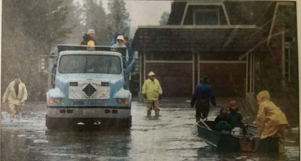 Residents who live on Colorado Court are evacuated Thursday, Jan. 2, 1997, with the help of a city of South Lake Tahoe dump truck while others return to their home to gather belongings.