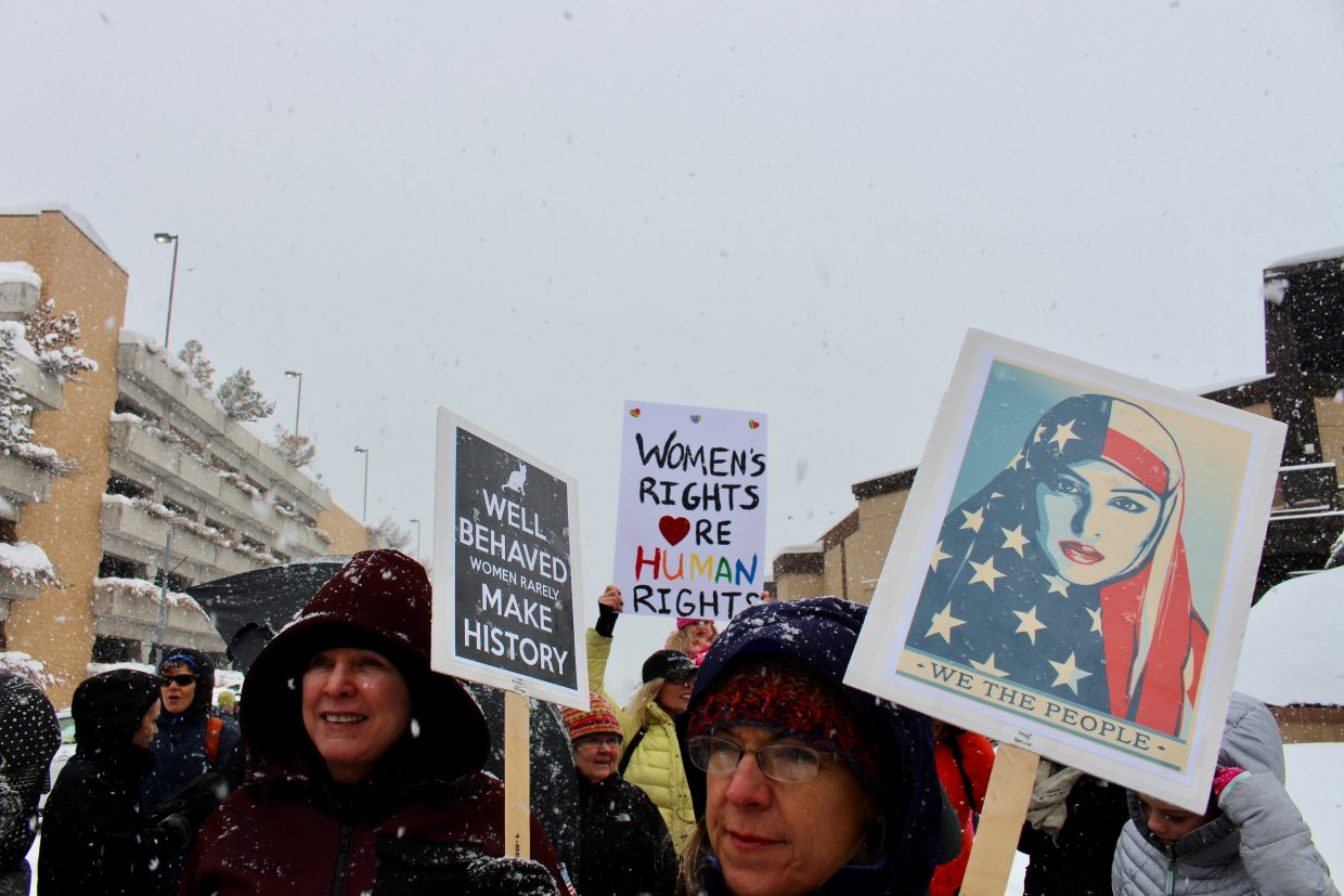 A group of women prepare to march with signs in hand.