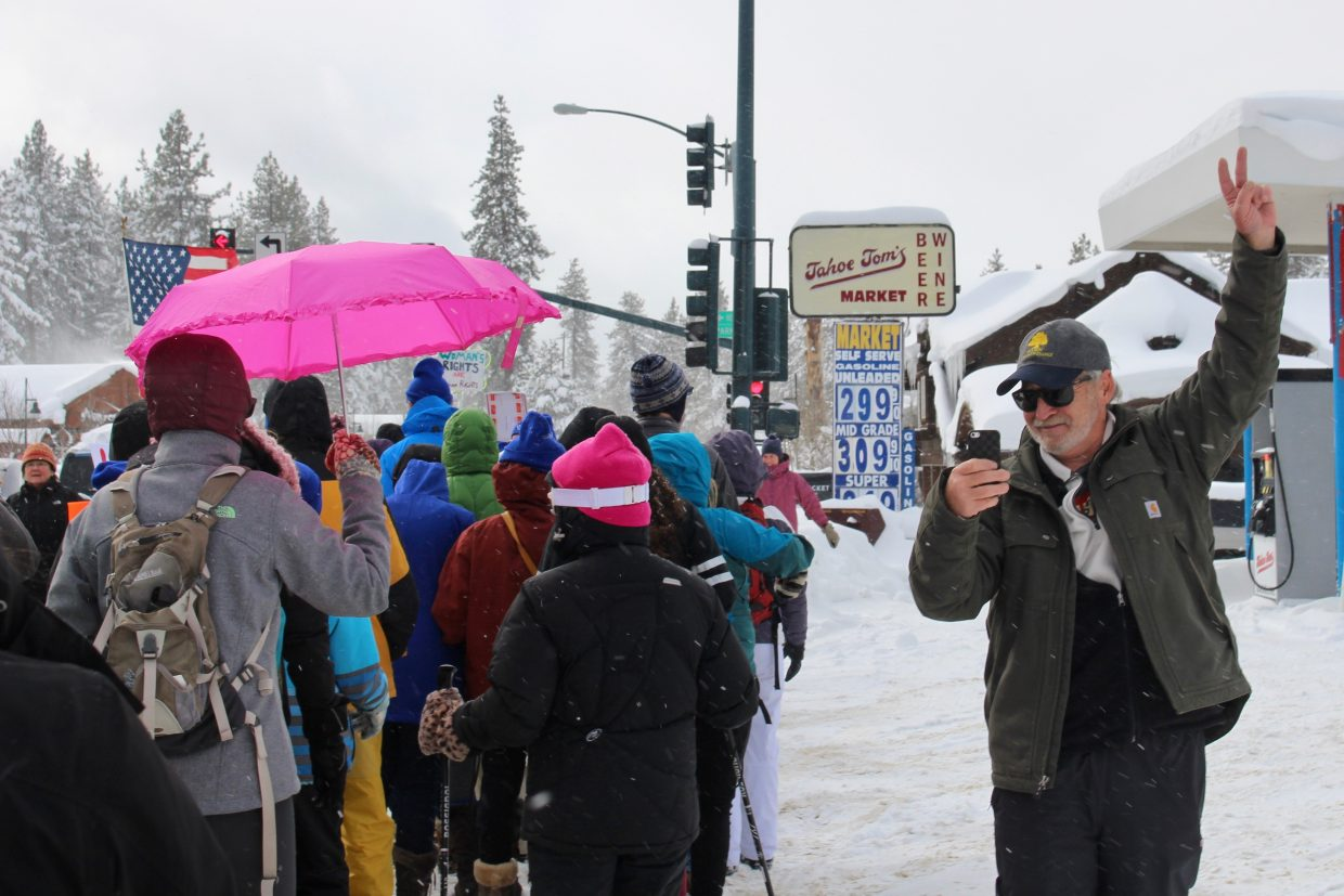 A man films the march as it progresses through the Stateline area.