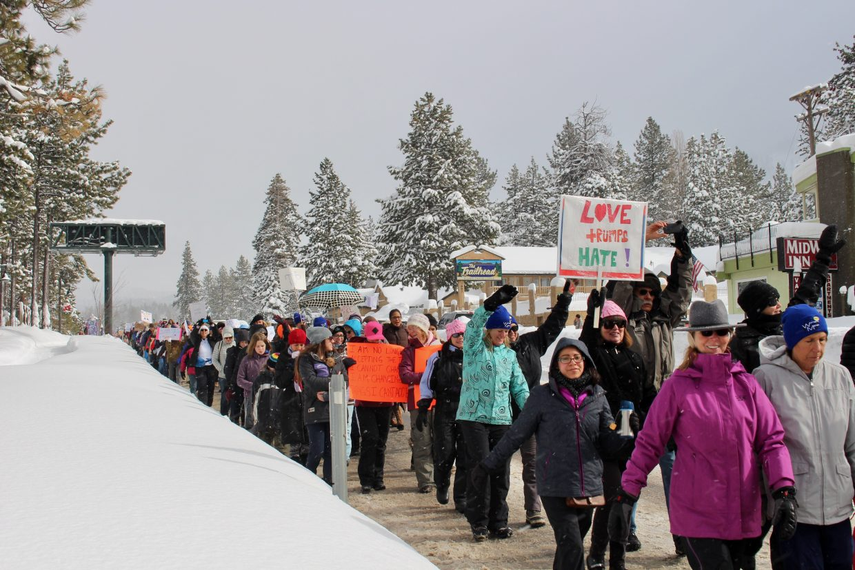 Marchers walk down Highway 50 in the snow.