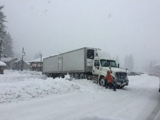 A semi-truck is stuck in a snow berm.