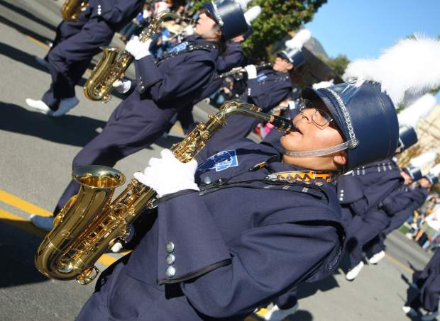 A member of the Carson High Marching Band plays while walking the parade route.