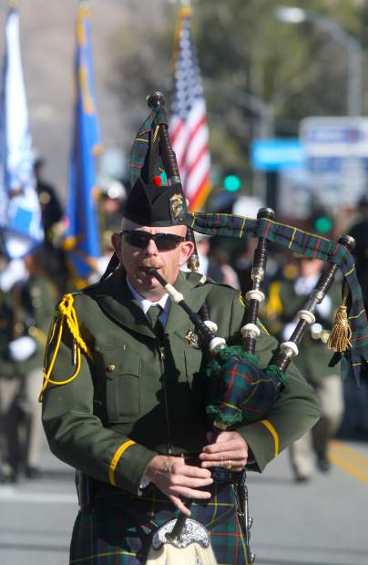 A bag piper leads the Color Guard at the front of the parade.