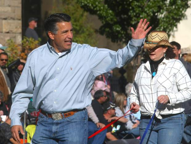 Gov. Brian Sandoval waves to the crowd as he walks the parade on Saturday.