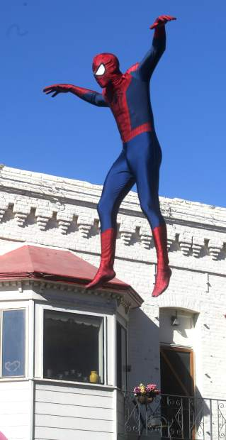 Spiderman leaps in the air above the crowds watching the parade.