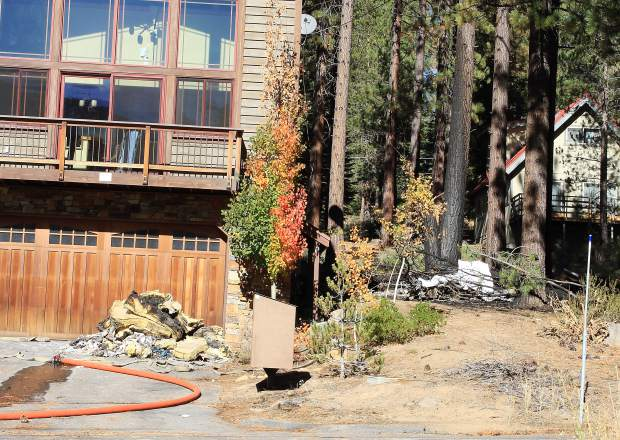 Plane wreckage sits beside the South Tahoe residence that caught fire as a result of the crash, on Saturday, Oct. 10.
