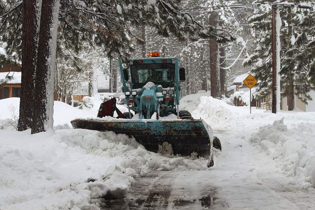 """A city of South Lake Tahoe plow clears a neighborhood street Wednesday. Nearby residents described the roads in the neighborhood that morning as """"touch and go."""""""