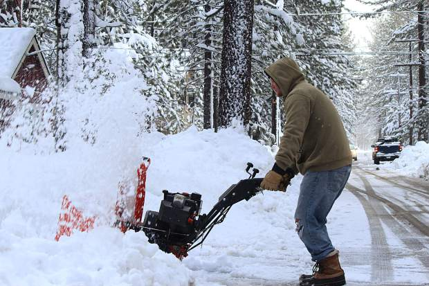 Nick Toland uses a snowblower to clear a driveway in South Lake Tahoe Wednesday, Jan. 11. Snow pounded the region through most of this week, forcing schools and some ski resorts to close due to unsafe conditions.