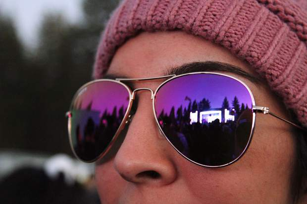A festival goer takes in the show beneath shades.