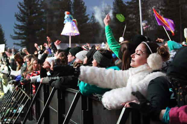 SnowGlobers dance against the fence at the main stage on Dec. 31.