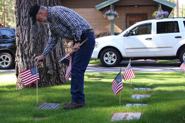 Vietnam War veteran Ric Patterson places a flag on the grave of a fellow veteran at Happy Homestead Cemetery in South Lake Tahoe on Thursday, May 25.