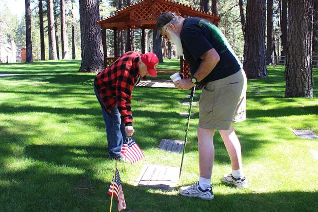 Two veterans place flags on a grave at Happy Homestead Cemetery in South Lake Tahoe in preparation for Memorial Day.