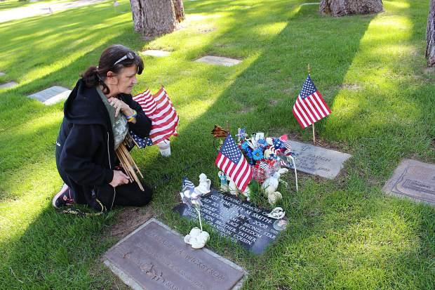 Patty Smith puts flowers and a flag at the grave of her son Sgt. Timothy Smith on Thursday, May 25, at Happy Homestead Cemetery. Sgt. Smith passed while serving in Iraq in April 2008.