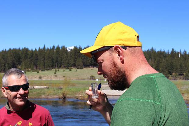 Zach McHenry smells a water sample from the Upper Truckee River as part of the community data-gathering event Tahoe Truckee Snapshots Day on Saturday, May 20. Volunteers collected water samples from tributaries around the basin and tested for temperature, pH level, nutrients, and bacteria.