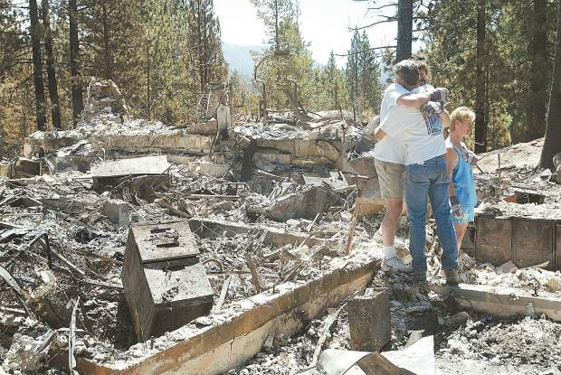 Dan Thrift/Tahoe Daily Tribune Standing in the middle of what used to be his home of 26 years, Dr. Martin Brooks, with gloves, gets a long hug from neighbor Jeff Glass on Friday morning who also lost his home in the Angora Fire. Right is Brooks' wife Karen.