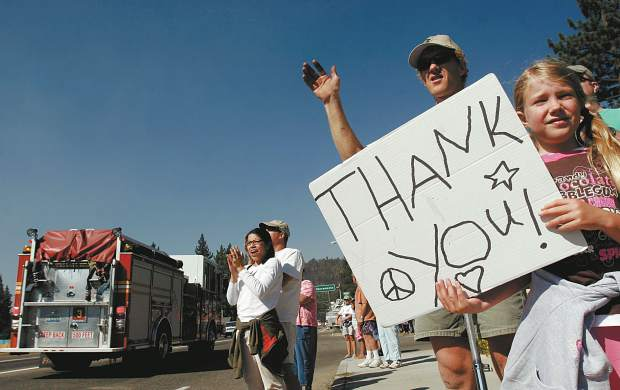 Trevor Clark/Tahoe Daily Tribune Kira and Allen Culp hold up a thank you sign and applaud firefighters as they pass by the