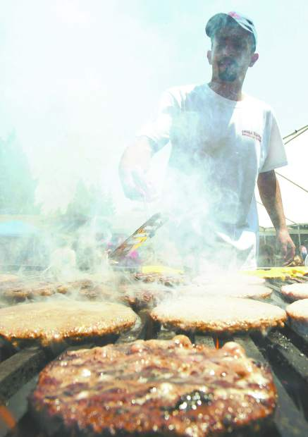 Dan Thrift/Tahoe Daily Tribune Isaac Margarito, a volunteer from K&K Enterprises, flips burgers Monday at the Meyers Community Get Together, a fund raiser for Angora Fire victums.