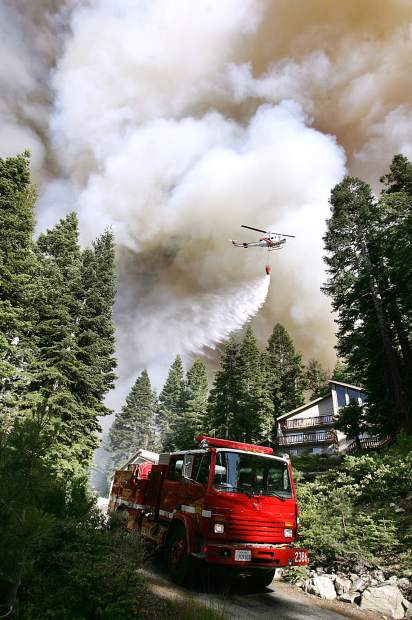 <b>Published Caption: </b>Cathleen Allison / Nevada Appeal Firefighters work to save homes threatened by the Angora fire on Sunday. <br><b>Photographer's Caption: </b><b>Published Caption: </b>Firefighters work to save homes in the area of Meyers, near South Lake Tahoe, Calif., Sunday, June 24, 2007. The Angora fire, driven by high winds, has destroyed an estimated 50 homes and continues to burn out of control. (AP Photo/Nevada Appeal, Cathleen Allison)** MAGS OUT, NO SALES ** <br><b>Photographer's Caption: </b>Firefighters work to save homes in the area of Meyers, near South Lake Tahoe, Calif., Sunday, June 24, 2007. The Angora fire, driven by high winds, has destroyed an estimated 50 homes and continues to burn out of control. (AP Photo/Nevada Appeal, Cathleen Allison)** MAGS OUT, NO SALES **