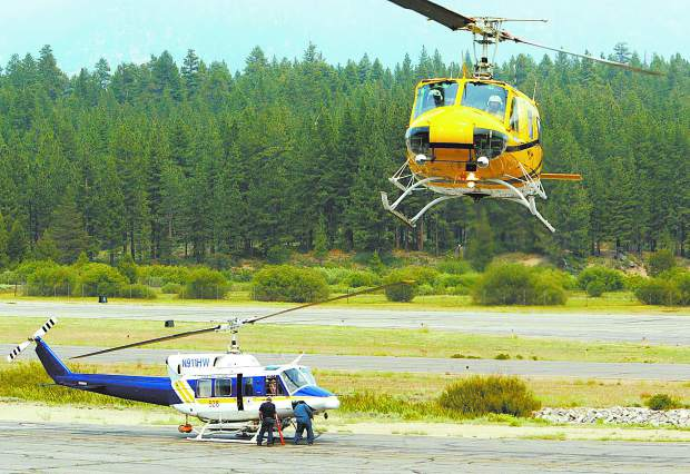 Dan Thrift/Tahoe Daily Tribune Helicopters land and prepare to take flight at Lake Tahoe Airport during the Angora Fire.