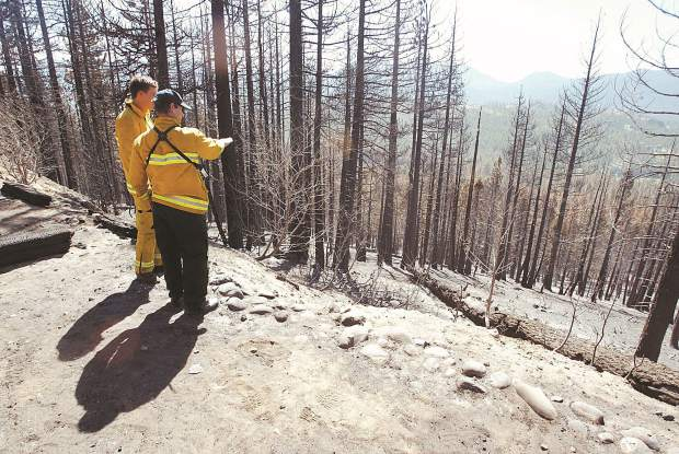 Dan Thrift/Tahoe Daily Tribune Luke Anderson,left, and Mike Mosca, both from Lake Valley Fire Protection District, survey the Angora Fire area Friday morning while making patrols on Heather Circle.