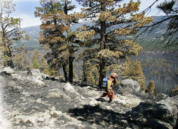 A firefighter negotiates the step terrain while looking for hot spots along Angora ridge during mop-up work on the Angora wildfire near South Lake Tahoe, Calif., Friday, June 29, 2007. (AP Photo/Nevada Appeal, Chad Lundquist)