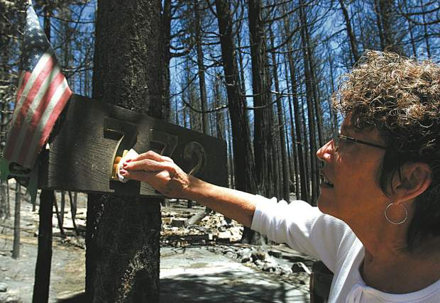 Trevor Clark/Tahoe Daily Tribune Alberta Rodriguez cleans off the address numbers to her burned down house on Saturday. The numbers and American flag are all that made it through the fire.