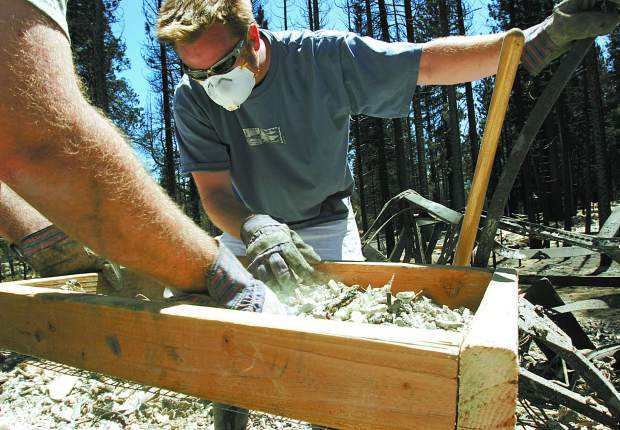 Trevor Clark/Tahoe Daily Tribune Chris Sennings sifts through debris from his home in search of any jewelry or family airlooms that might be salvageable on Saturday.