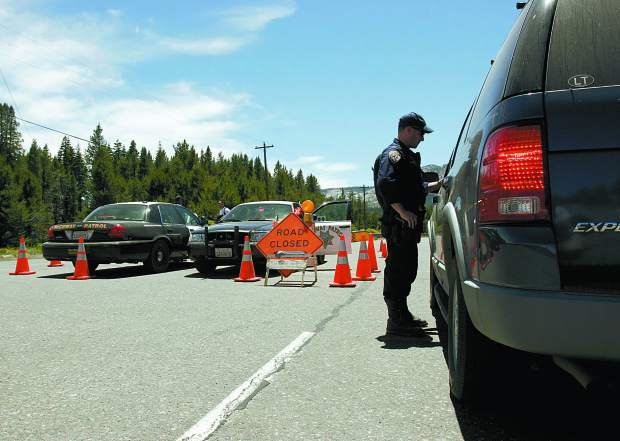 Trevor Clark/Tahoe Daily Tribune Officer Kevin Dwyer makes sure the vehicle at the road block is a resident of the area effected by the Angora Fire at the junction of Sawmill Road and Lake Tahoe Boulevard on Sunday.