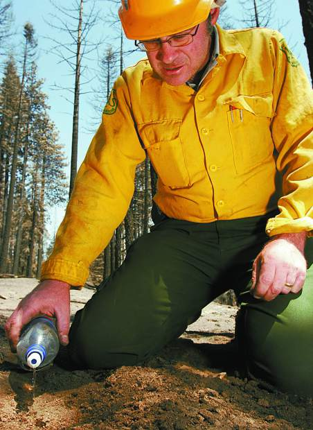 Trevor Clark/Tahoe Daily Tribune Forest Service Soil Scientist Todd Ellsworth checks the water repellancy of the soil in the Angora Creek area on Saturday. High water repellancy can lead to higher levels of erosion.