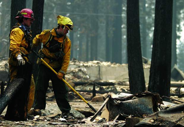 Brad Shisholm and Josh Scarboro of Squaw Valley Fire Protection District mop up the smouldering remains of a home in the Mountain View Estates Tuesday after it was destroyed by the Angora fire.