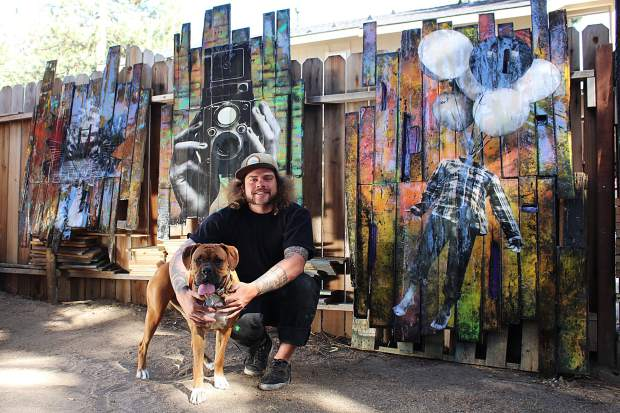 Mixed media artist Will Eichelberger, pictured here in his outdoor studio with his dog, combines large prints of his photographs with graffiti-style painting.