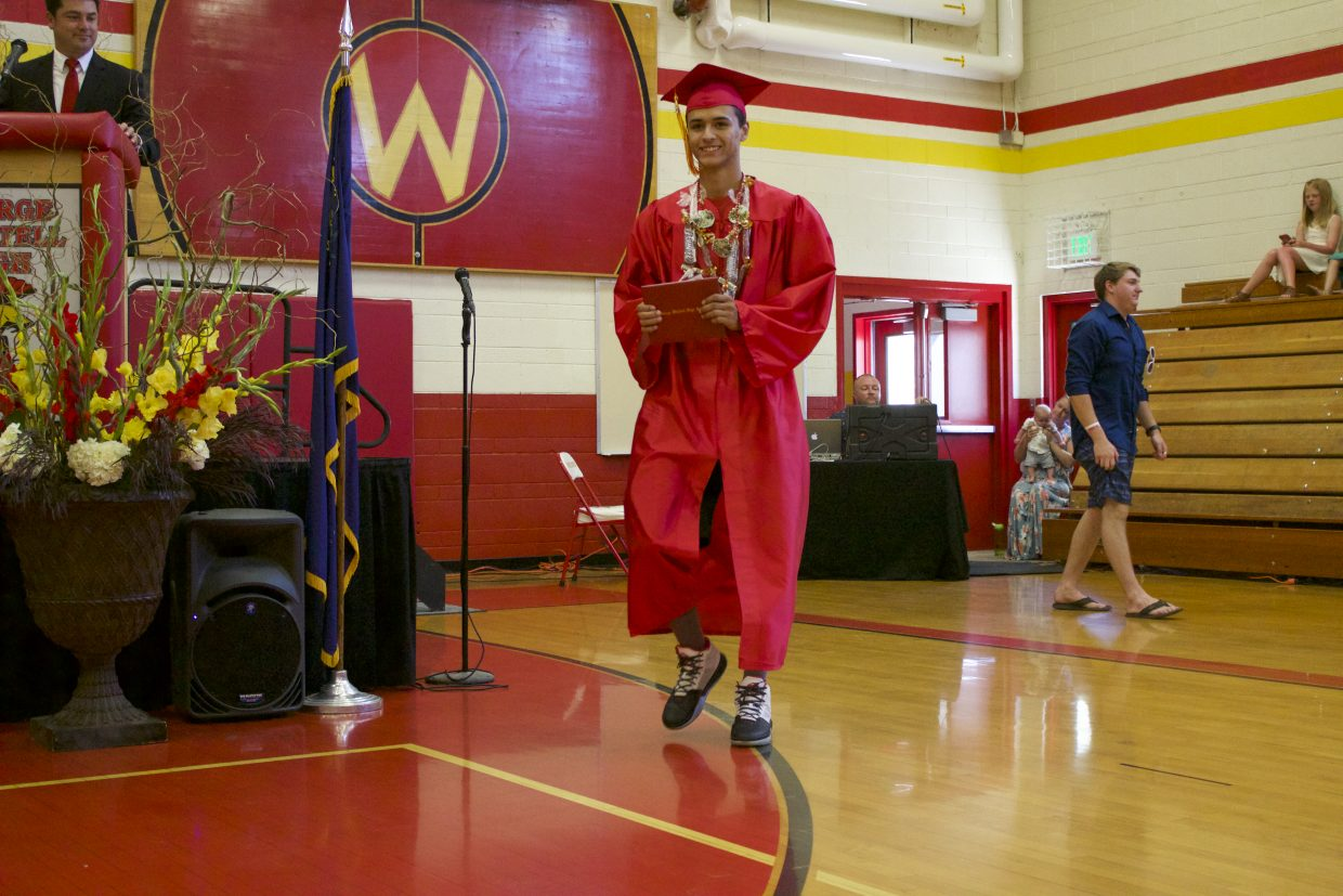 Dismas Womack holds his diploma with pride moments after crossing the stage.