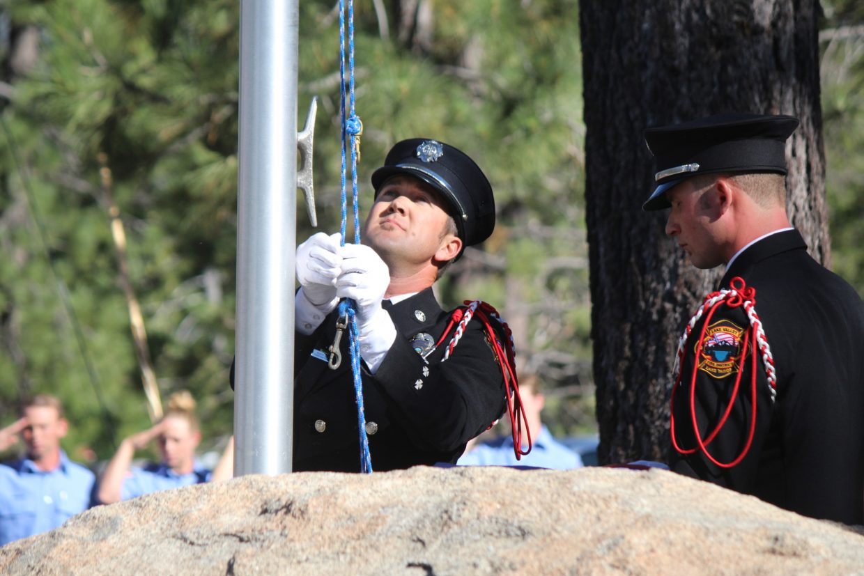 Dusty LaChapelle, a firefighter/paramedic with the Lake Valley Fire Protection District, prepares to raise the American Flag Saturday, June 24.