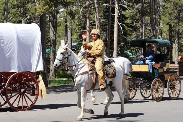 Some members of the organization travel by wagon, while others ride on horses.