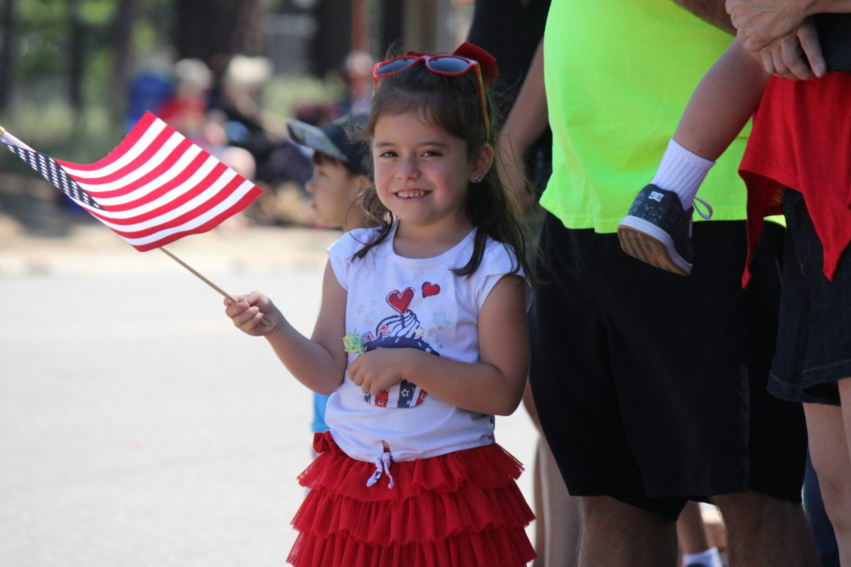 Karinna Pacheco, of Carson City, waves a flag as floats in the annual Fourth of July parade make their way down Al Tahoe Boulevard Tuesday.