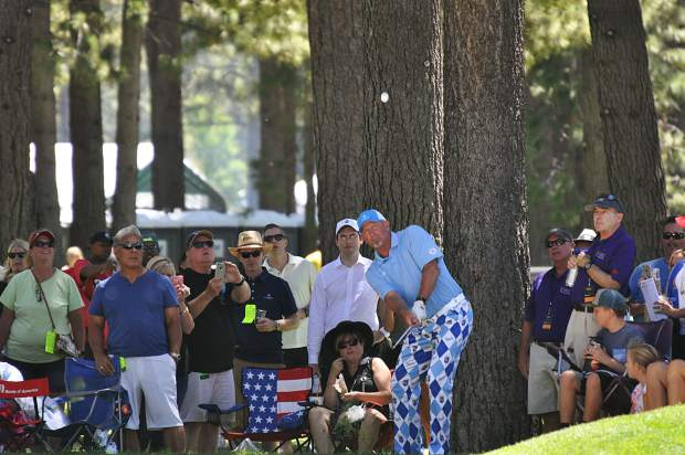 Former MLB pitcher Bret Saberhagen hits a chip shot as spectators watch Saturday.