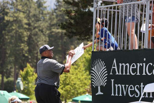 Charles Barkley signs an autograph for a strategically placed youngster at the exit of the 18th green Friday.