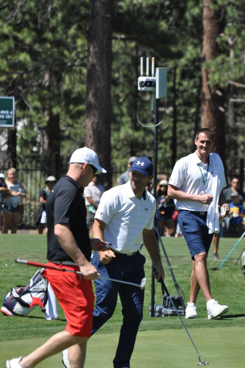 Tony Romo goes for a fist bump while leaving the green.