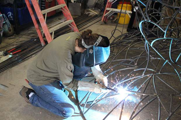 Levine welds a piece of steel on her sculpture, which she has named