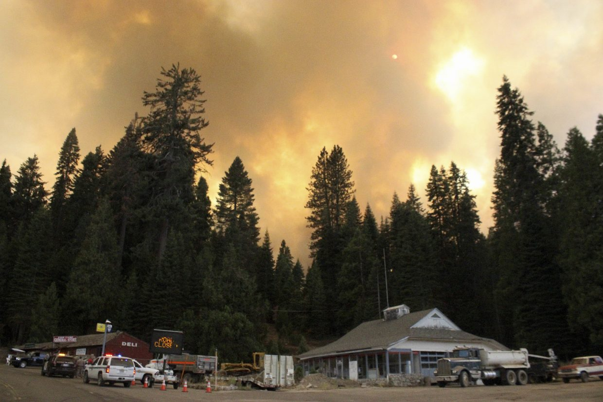 In this Tuesday, Aug. 29, 2017 photo, smoke rises from a wildfire behind the Fish Camp General Store near Yosemite National Park in Fish Camp, Calif. The wildfire is among a series of wildfires burning across the U.S. West.