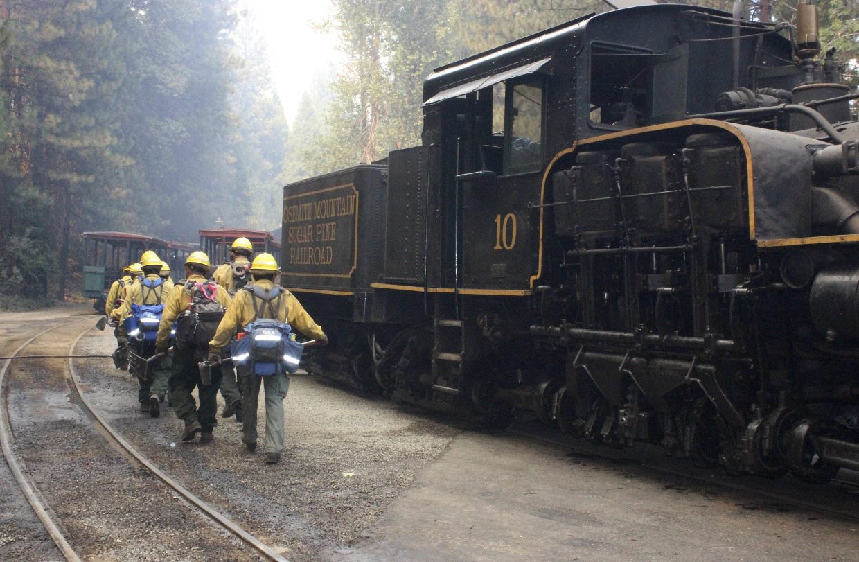 In this Tuesday, Aug. 29, 2017 photo, U.S. Forest Service hand crew out of Fresno, Calif., walks toward a small spot fire at the Yosemite Mountain Sugar Pine Railroad in Fish Camp, Calif. The wildfire is among a series of wildfires burning across the U.S. West.