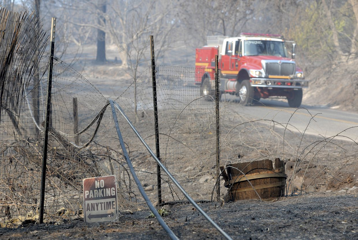 A fire truck working on a wildfire drives past downed power lines along Lumpkin Road near Oroville, Calif., Wednesday, Aug. 30, 2017. The wildfire is among a series of wildfires burning across the U.S. West.