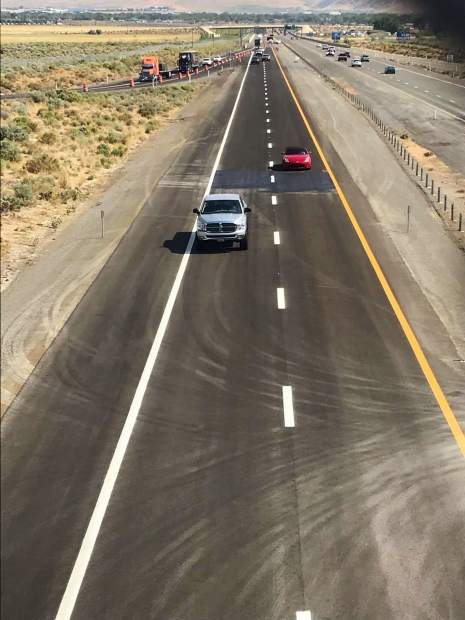 Around 10:12 a.m., Nevada Department of Transportation crews lift traffic cones for access of the newly paved last leg of I-580.