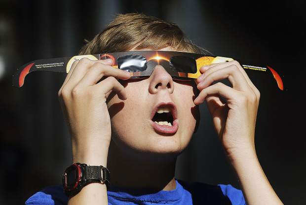Eclipse glasses, which are thousands of times darker than regular sunglasses, are necessary to avoid eye damage during the solar eclipse.