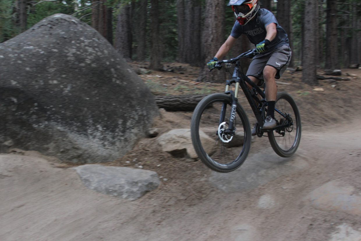 A biker clears a jump on his mountain bike.